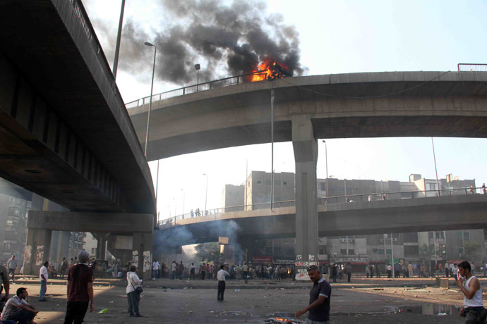 Egyptian Muslim brotherhood supporters of Egypt's ousted president Mohamed Morsi look up at a vehicle burning on six October bridge during clashes with riot police after security forces dispersed Morsi supporters on August 14, 2013 in Cairo. (AFP Photo/Khaled Kamel)