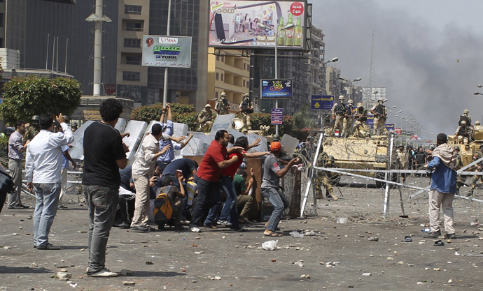 Members of the Muslim Brotherhood and supporters of ousted Egyptian President Mohamed Morsi throw stones at riot police and the army during clashes around the area of Rabaa Adawiya square, where they are camping, in Cairo August 14, 2013. (Reuters/Asmaa Waguih)