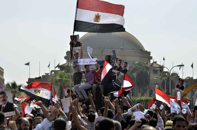 Supporters of Islamist Egyptian President Mohamed Morsi hold pictures of him during a rally by mainly Muslim Brotherhood partisans outside Cairo University on June 2, 2013. (AFP Photo / Mohamed El-Shahed)