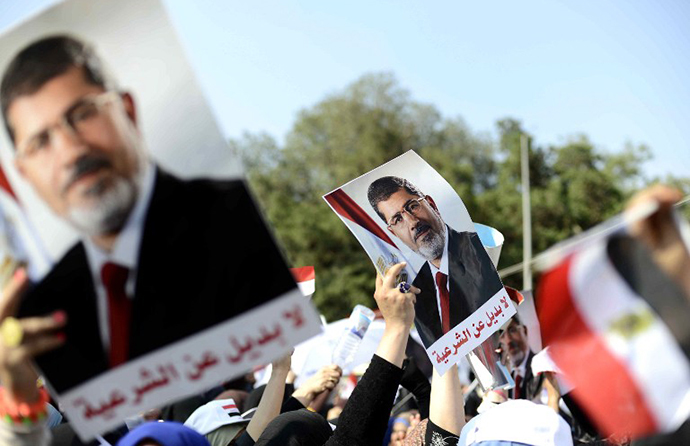 Supporters of Islamist Egyptian President Mohamed Morsi holds up his image during a rally outside Cairo University on June 2, 2013. (AFP Photo / Mohamed El-Shahed)