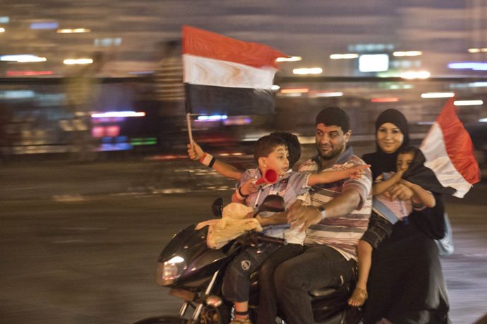 An Egyptian family on motorcycle celebrates in Cairo on July 3, 2013 after a broadcast confirming that the army will temporarily be taking over from the country's first democratically elected president Mohammed Morsi (AFP Photo / Khaled Desouki)