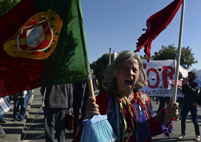 A demonstrator shouts slogans and waves a Portuguese flag on a broom stick during a protest against governments policies in front of Belem presidential palace in Lisbon on May 20, 2013, as Portuguese President Anibal Cavaco Silva (unseen) gathers the State Coucil, his advisers body. (AFP Photo)