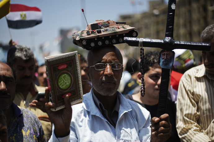An Egyptian man, bearing a toy tank on his head, holds a cross (R) and a copy of the Koran, Islam's holy book, as people gather in Cairo's landmark Tahrir square after a night of celebrations following the toppling of ousted Egyptian president Mohamed Morsi on July 4, 2013 (AFP Photo / Gianluigi Guercia)