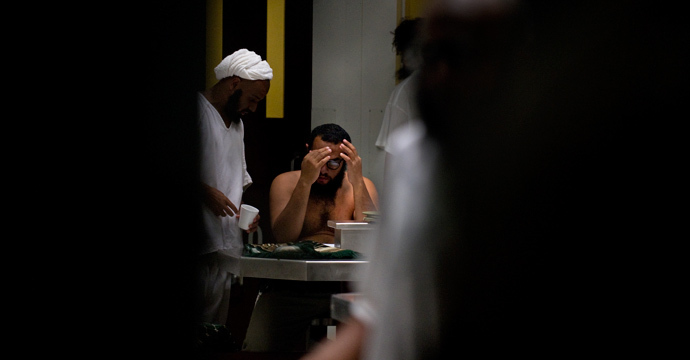 In this photo reviewed by US military officials, detainees gather during lunch in a communial area inside Camp VI at the US Detention Center in Guantanamo Bay, Cuba, March 30, 2010 (AFP Photo / Paul J. Richards)