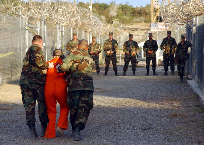U.S. Army Military Police escort a detainee to his cell during in-processing to the temporary detention facility at Camp X-Ray in Naval Base Guantanamo Bay (Reuters / Stringer / Files)