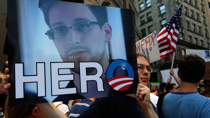 "A demonstrator holds a sign with a photograph of former U.S. spy agency NSA contractor Edward Snowden and the word ""HERO"" during Fourth of July Independence Day celebrations in Boston, Massachusetts July 4, 2013.(Reuters / Brian Snyder)"
