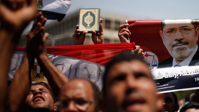 Protesters, who support former Egyptian President Mohamed Morsi, with flags and posters march near Cairo University after Friday prayers in Cairo July 5, 2013.(Reuters / Suhaib Salem)
