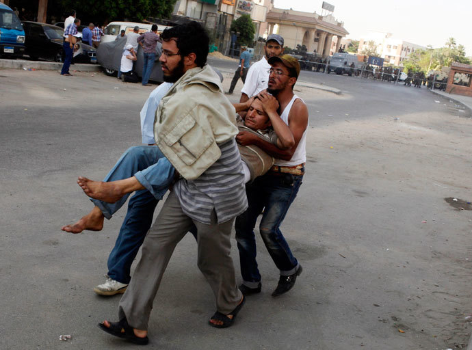 Protesters, who support former Egyptian President Mohamed Mursi, carry an injured man during clashes outside the Republican Guard building in Cairo July 5, 2013.(Reuters / Asmaa Waguih)