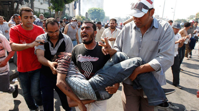 Protesters who support former Egyptian President Mohamed Mursi carry an injured man during clashes outside the Republican Guard building in Cairo July 5, 2013.(Reuters / Louafi Larbi)