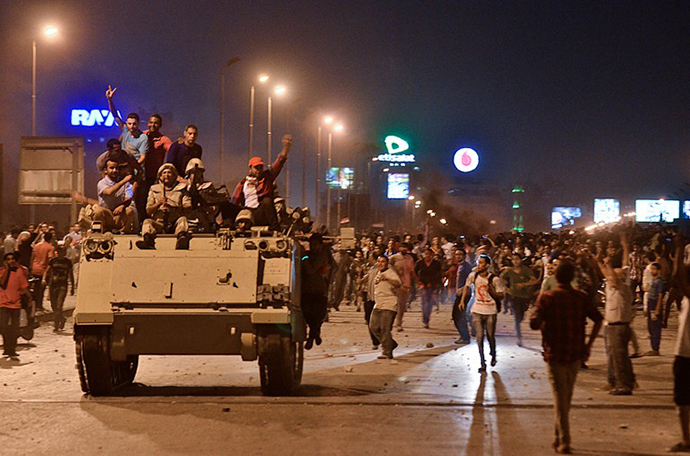 Protesters cheer upon the arrival of the Egyptian Security Forces during clashes between ousted president Mohamed Morsi supporters and anti-Morsi protesters near Egypt's landmark Tahrir square on July 5, 2013 in Cairo, Egypt. (AFP Photo / Mohamed El-Shahed)