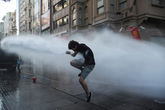 A protesters takes cover from a water cannon jet during clashes with police on Istiklal Avenue in Istanbul on July 6, 2013. (AFP Photo/Bulent Kilic)