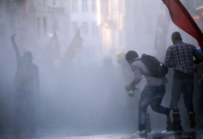 Protesters take cover from a water cannon during clashes with police on Istiklal Avenue in Istanbul on July 6, 2013. (AFP Photo/Bulent Kilic)