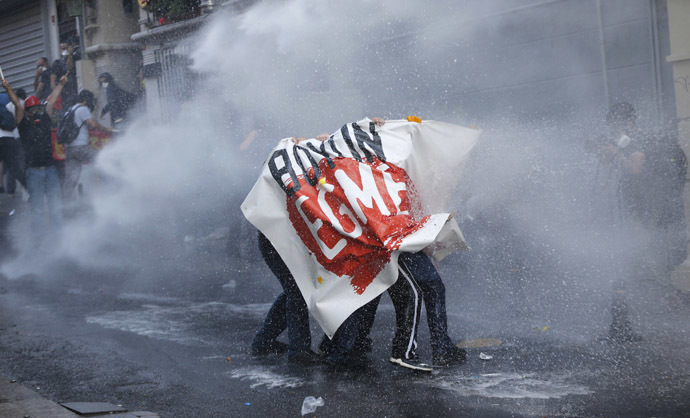 "Demonstrators hold a banner reading, ""Don't bow down"", as riot police use water cannon to disperse them during a protest in central Istanbul July 6, 2013. (Reuters/Murad Sezer)"