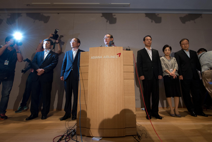 Asiana Airlines CEO Yoon Young-doo (C) stands with other executives as he makes a statement during a press conference at the company headquarters building in Seoul on July 7, 2013 (AFP Photo / Ed Jones)