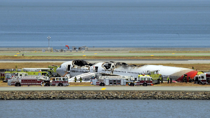 An Asiana Airlines Boeing 777 is seen on the runway at San Francisco International Airport after crash landing on July 6, 2013. (AFP Photo/Josh Edelson)