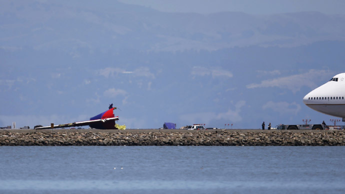 An airliner stands by as investihgators examine the wreckage of the tail section of an Asiana Airlines Boeing 777 which crash landied at San Francisco International Airport in San Francisco, California July 6, 2013. (Reuters/Stephen Lam)