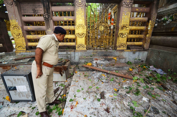 An Indian policeman looks at debris left after several low intensity explosions took place at at the Bodh Gaya Buddhist temple complex injuring two people on July 07,2013 (AFP Photo / STR)