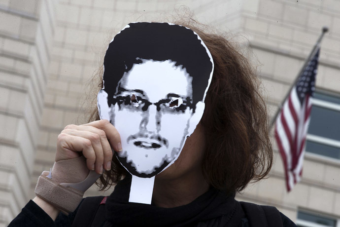 A woman holds a portrait of former U.S. spy agency contractor Edward Snowden in front of her face as she stands in front of the U.S. embassy during a protest in Berlin, July 4, 2013. (Reuters/Thomas Peter)