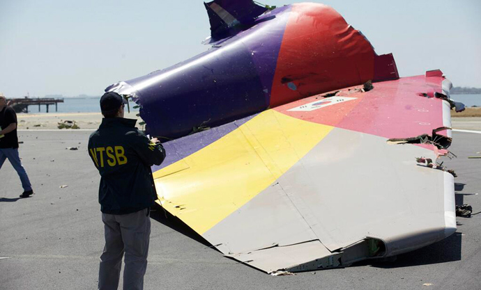 A National Transportation Safety Board (NTSB) investigator looks at the tail section of the Asiana Airlines Flight 214 that crashed at San Francisco International Airport in San Francisco, California in this handout photo released on July 7, 2013 (Reuters / NTSB / Handout via Reuters)
