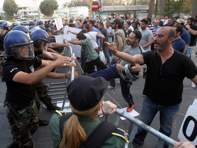 Demonstrators scuffle with the police after lawmakers by majority vote approved an EU bailout, outside the parliament in the Cypriot capital of Nicosia (Reuters / Andreas Manolis)