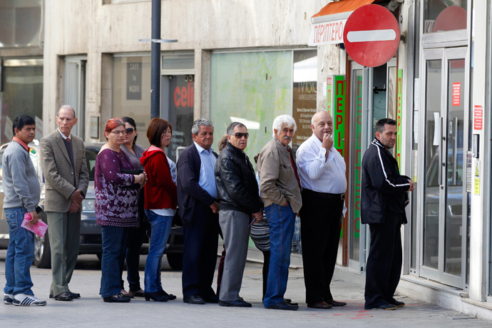 Depositors wait for the opening of a branch of Laiki Bank in Nicosia (Reuters / Bogdan Cristel)