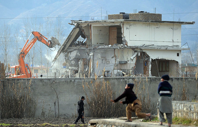 Young Pakistani boys play near demolition works on the compound where Al-Qaeda chief Osama bin Laden was slain last year in the northwestern town of Abbottabad on February 26, 2012. (AFP Photo / Aamir Qureshi)