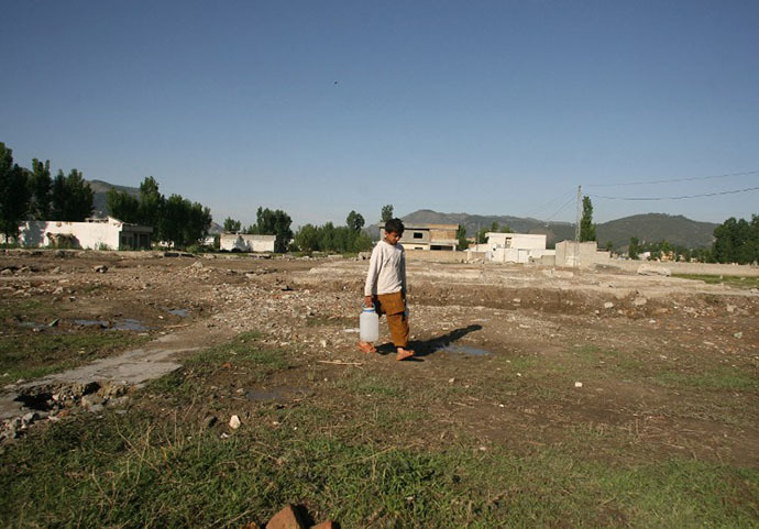 A Pakistani boy carries water cans at the site of the demolished compound of slain Al-Qaeda leader Osama bin Laden in northern Abbottabad on May 2, 2012. (AFP Photo / Sajjad Qayyum)