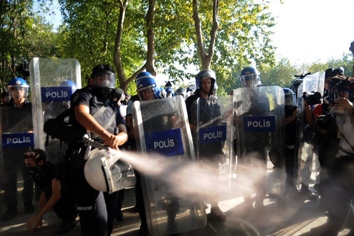 Turkish riot policemen use gas to disperse demonstrators at the Taksim Gezi Park on Istiklal Avenue in Istanbul on July 8, 2013. (AFP Photo / Bulent Kilic)