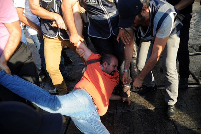 Turkish riot policemen arrest a protestor during clashes with police on Taksim sqaure in Istanbul on July 8, 2013. (AFP Photo / Bulent Kilic)