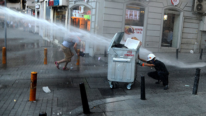 A protestor take cover from water cannon during clashes with police officers on Istiklal avenue, in Istanbul on July 8, 2013. (AFP Photo / Bulent Kilic)