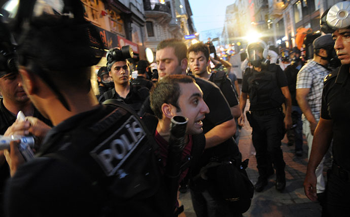 Turkish riot policemen arrest a protestor during clashes with police on Taksim square in Istanbul on July 8, 2013. (AFP Photo / Bulent Kilic)