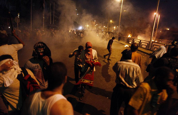 People run for cover as security forces fire tear gas after shooting to disperse Islamist supporters of ousted president Mohamed Morsi outside the Republican Guard headquarters in Cairo in the early hours of July 8, 2013. (AFP Photo / Mahmoud Khaled)