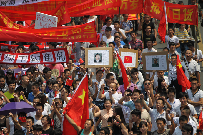 "Chinese demonstrators carry Chinese national flags and shout slogans during a protest against Japan's ""nationalizing"" of the Diaoyu islands, also known as Senkaku in Japan, in Wenzhou, east China's Zhejiang province on September 18, 2012 (China out / AFP Photo)"