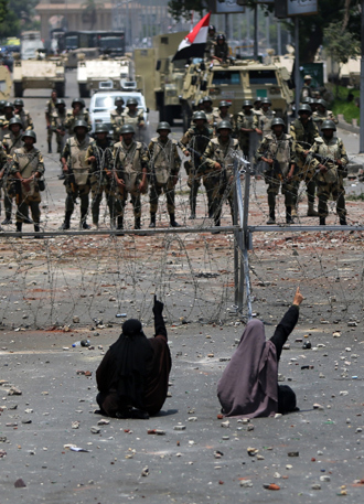 Two veiled Egyptian women, supporters of deposed president Mohamed Morsi, sit in front police standing behind barbed wire fencing that blocks the access to the headquarters of the Republican Guard in Cairo on July 8, 2013 (AFP Photo / Mahmud Hams)