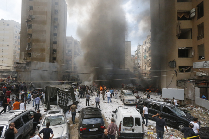 Firefighters and residents gather at the site of an explosion in Beirut's southern suburb neighbourhood of Bir al-Abed on July 9, 2013 (AFP Photo / Str)