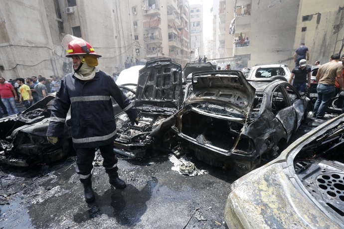 A firefighter stands after extinguishing fire from vehicles at the site of an explosion in Beirut's southern suburb neighbourhood of Bir al-Abed on July 9, 2013 (AFP Photo / Str)