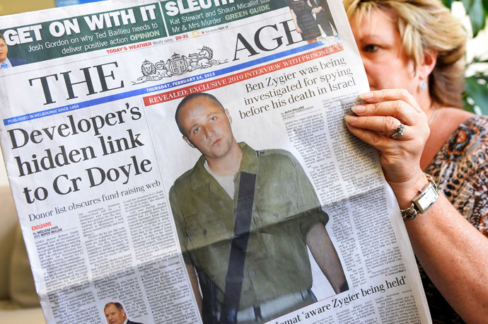 In this photo illustration taken in Sydney on February 14, 2013, a woman poses with an Australian newspaper showing the front page story of Ben Zygier, as Israel confirms it jailed a foreigner in solitary confinement on security grounds who later committed suicide, with Australia admitting it knew one of its citizens had been detained. (AFP Photo/William West)