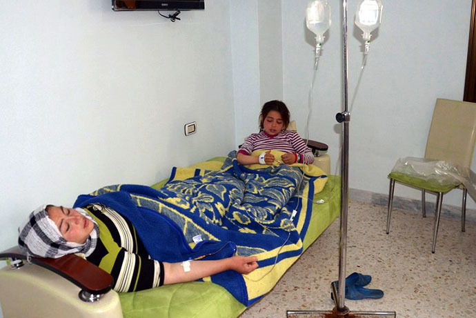 In this image made available by the Syrian News Agency on March 19, 2013, a woman and a girl rest on a mattress at a hospital in the Khan al-Assal region in the northern Aleppo province, as Syria's government accused rebel forces of using chemical weapons for the first time. (AFP Photo / SANA)