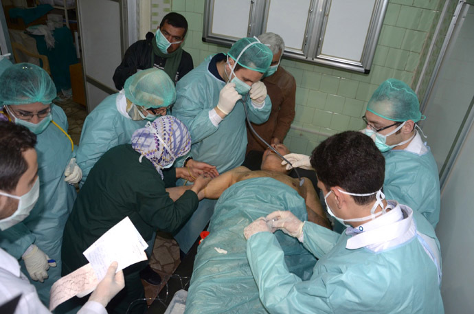 In this image made available by the Syrian News Agency (SANA) on March 19, 2013, medics and other masked people attend to a man at a hospital in Khan al-Assal in the northern Aleppo province, as Syria's government accused rebel forces of using chemical weapons for the first time. (AFP Photo/SANA)
