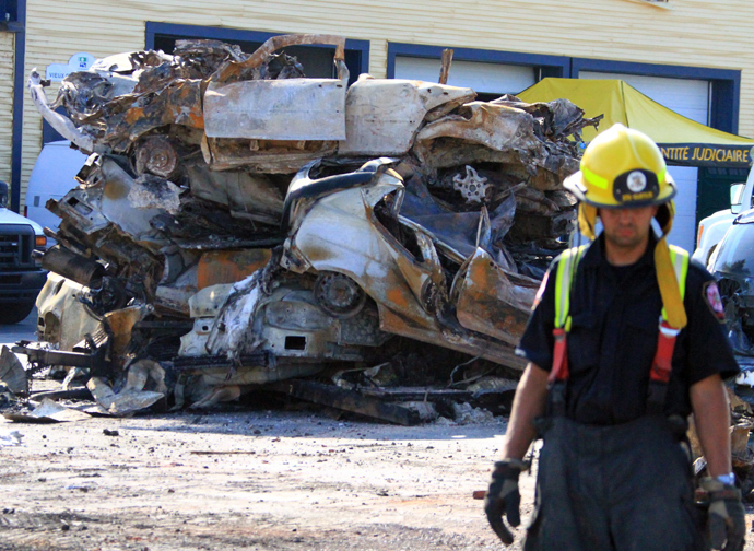 This photo provided July 8, 2013 by Surete du Quebec, shows a firefighter and a pile of burnt cars and debris left from a train derailment and exposion in Lac-Megantic, Quebec, Canada (AFP Photo)