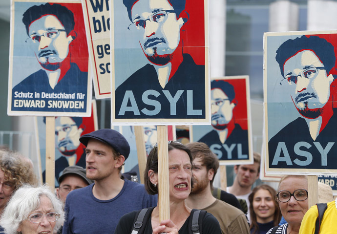 Demonstrators hold banner during protest rally in support of former U.S. spy agency NSA contractor Edward Snowden in Berlin July 4, 2013. (Reuters/Tobias Schwarz)