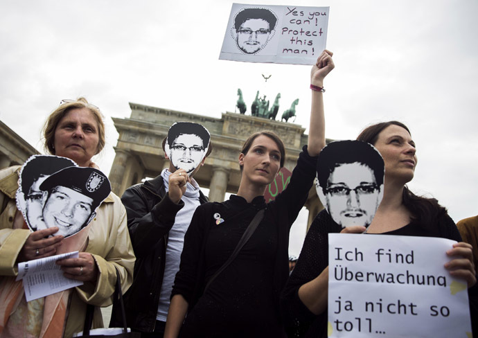 People hold placards in support of former U.S. spy agency contractor Edward Snowden during a protest in front of Brandenburg Gate in Berlin, July 4, 2013. (Reuters/Thomas Peter)