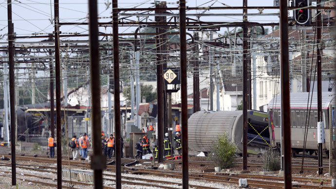 Rescuers work on the site of a train accident in the railway station of Bretigny-sur-Orge on July 12, 2013 near Paris. (AFP Photo / Kenzo Tribouillard)