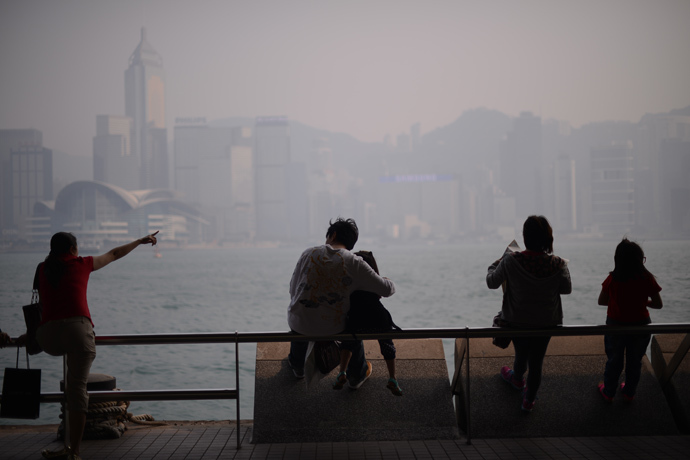 People sit in front of the city's skyline shrouded in a dense blanket of toxic smog in Hong Kong on April 15, 2013 (AFP Photo / Philippe Lopez)