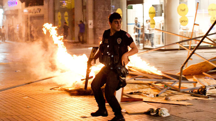 A Turkish riot policeman clashes with Turkish protestors on July 14, 2013 on Istiklal Avenue in the center of Istanbul.(AFP Photo / Gurcan Oztur)