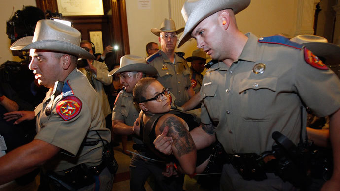 Police carry an abortion rights protester down the stairs of the State Capitol after the state Senate passed legislation restricting abortion rights in Austin, Texas early July 13, 2013.(Reuters / Mike Stone)