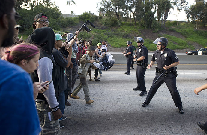 Police officers hold a line against protestors on the 10 Freeway after demonstrators angry at the acquittal of George Zimmerman in the death of black teen Trayvon Martin walk onto the 10 Freeway stopping highway traffic, in Los Angeles, California July 14, 2013. (AFP Photo / Robyn Beck)