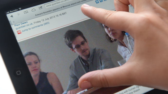 A journalist looks at a display with a picture of former CIA employee Edward Snowden (RIA Novosti)