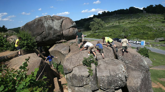 "Boy scouts from Winchester, Virginia climb atop the boulders of ""Devil's Den"", in Gettysburg, Pennsylvania. (AFP Photo / John Moore)"