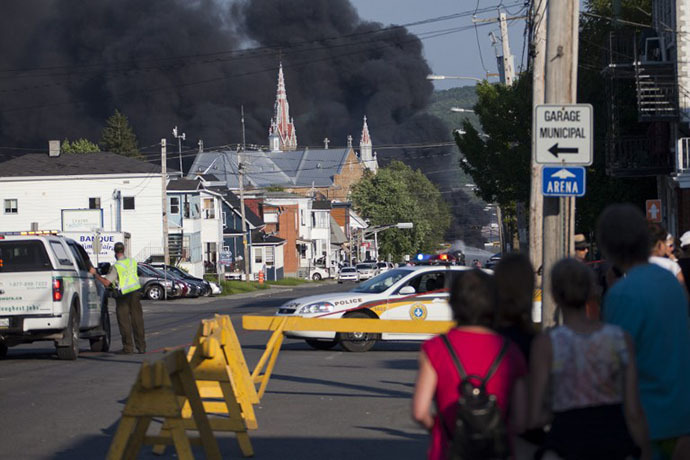 Residents watch rising smoke after a freight train loaded with oil derailed in Lac Megantic in Canada's Quebec province on July 6, 2013, sparking explosions that engulfed about 30 buildings in fire. (AFP Photo / FranÁois Laplante-Delagrave)